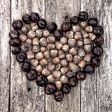 chestnuts-acorns-forming-heart-wooden-background-39688723