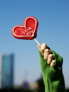 xpacifica-woman-s-hand-holding-up-a-red-heart-shaped-lollipop